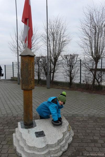 Pomnik zaślubin Polski z morzem. Sebuś wkłada rękę do obrączki.