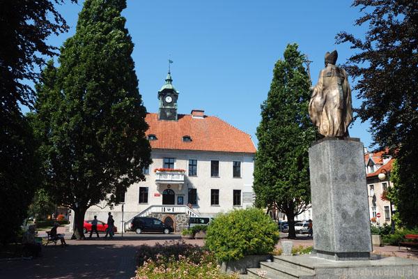 Mrągowski ratusz (XIX w.), przed nim pomnik Jana Pawła II.