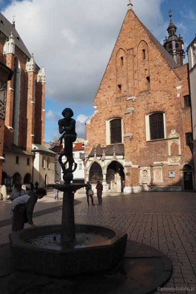 Uroczy Plac Mariacki z kościołem Św. Barbary i figurką krakowskiego żaka na studzience.