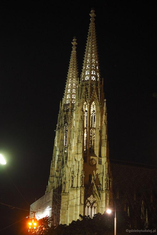 Oświetlone neogotyckie wieże Votivkirche wyciągają nad na spacer.