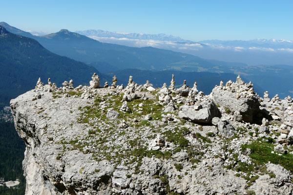 Turyści w Dolomitach lubią układać kopczyki, w tle na horyzoncie Alpy.