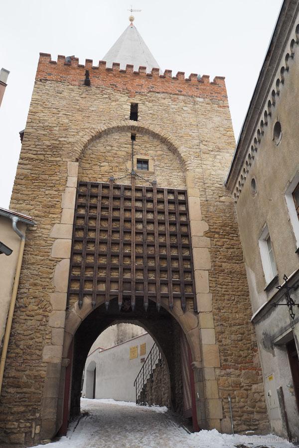 Brama została wzmocniona żelazną kratą i wieżą z krenelażem.
